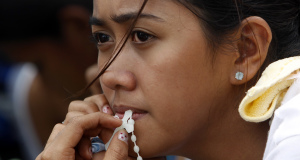 Woman with rosary wait for evacuation flight from tyhoon-battered city in Philippines